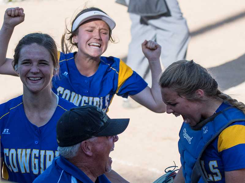 LON AUSTIN/CENTRAL OREGONIAN - McKuenzie McCormick, Matney Searcy, Caitlyn Elliott and assistant coach Gary White celebrate following the Cowgilrs' win over McLoughlin on Friday.