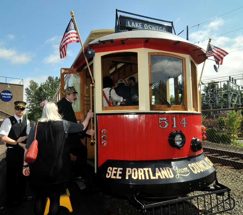 REVIEW PHOTO: VERN UYETAKE - Trolley motormen Gage Geist (left) and Neil Berlin assist riders boarding the Willamette Shore Trolley for its first passenger run of the season last week.