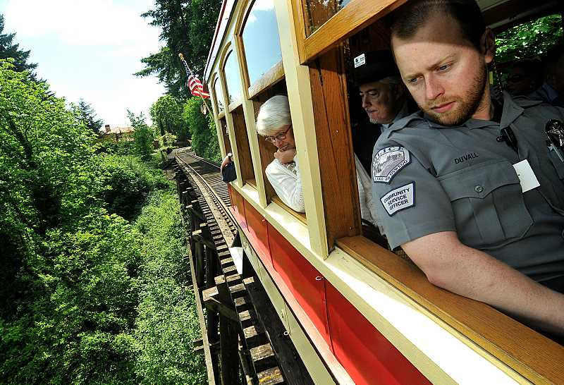 REVIEW PHOTO: VERN UYETAKE - Lake Oswego Police CSO Cole Duvall (right) and Peggy and Keith Dickerson gaze out of windows as the trolley crosses a trestle along the shore of the Willamette River.