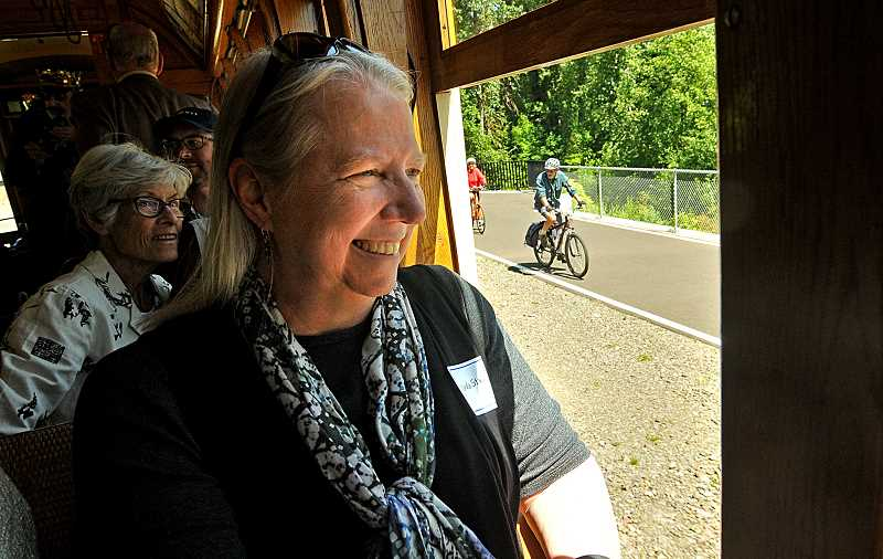 REVIEW PHOTO: VERN UYETAKE - Linda Strand enjoys the view as the trolley rumbles past a bike path near the Sellwood Bridge.