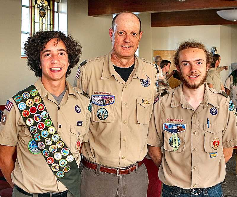 DAVID F. ASHTON - On the night of their investiture as Eagle Scouts, Nicklaus Hart and Ian Legros flank Troop 64 Scoutmaster Tom Armstrong.