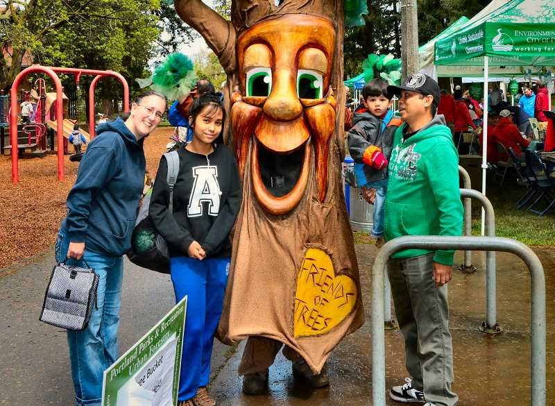 DAVID F. ASHTON - The Ortiz family spends a moment with the Friends of Trees mascot, Garry Oak.