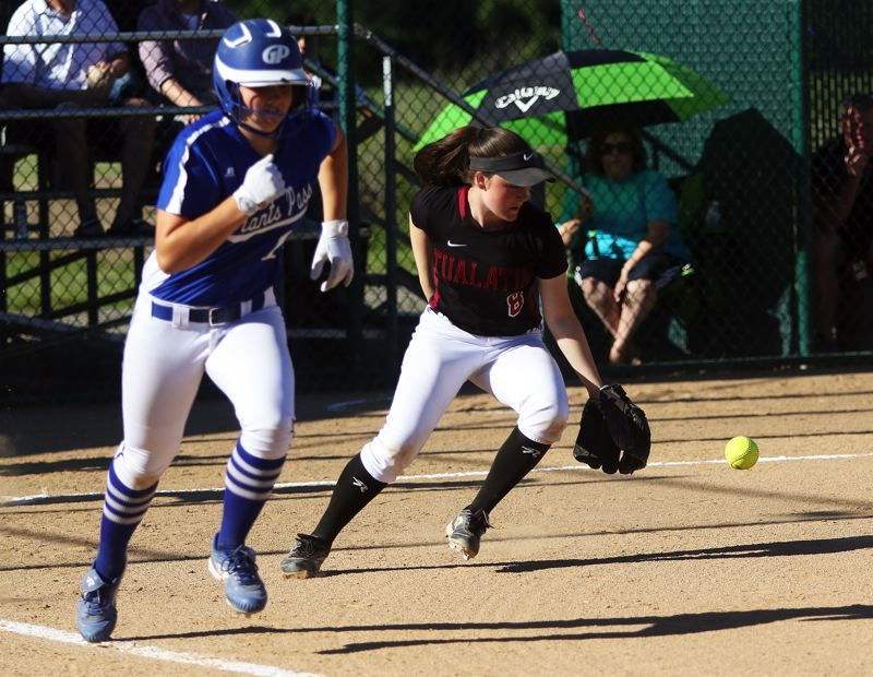 DAN BROOD - Tualatin third baseman Taylor Alton (right) looks to chase down a bunt by Grants Pass freshman Devin Ireland.