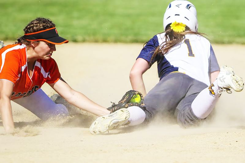 PHOTO CREDIT: JOAQUIN AGUILAR-FLORES - Indians sophomore Peyton Fisher, left, attempts a tag of Henley senior Jess Pettigrew.
