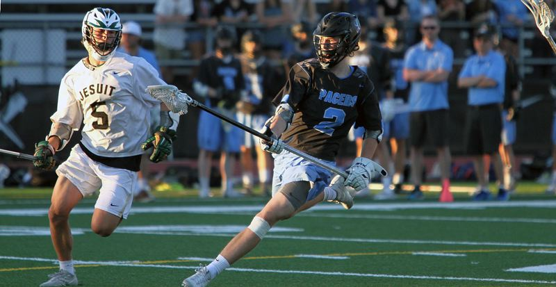 REVIEW PHOTO: MILES VANCE - Lakeridge senior Sean Scadden races past Jesuit's Tucker Dordevic during the Pacers' 11-10 playoff loss at Jesuit High School on Friday.