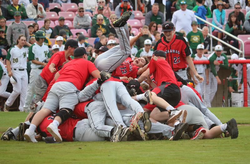 PMG PHOTO: JIM BESEDA - Clackamas' James Gebe (No. 13) rides the top of the pile as the Cavaliers celebrate their 5-1 win over West Linn in the Class 6A state championship baseball game at Volcanoes Stadium in Keizer on Saturday.