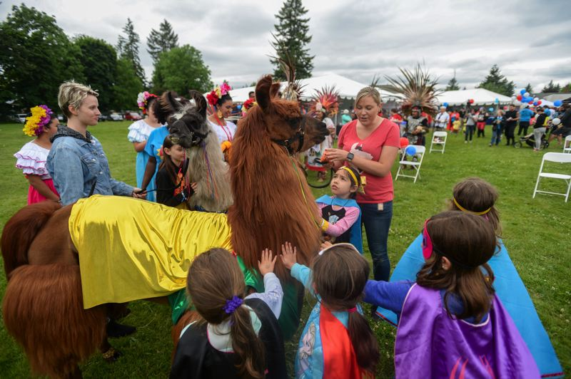 OUTLOOK PHOTO: JOSH KULLA - Shannon Joy of Mountain Peaks Therapy Llamas and Alpacas shows off the popular llamas Rojo (front) and Smokey as a crowd of children gathers around during Rock the Block on Saturday.