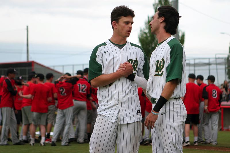 TIDINGS PHOTO: MILES VANCE - West Linn seniors Tim Tawa (left) and Chase Cosner shake hands following their team's 5-1 loss to Clackamas in the Class 6A state championship game at Volcanoes Stadium in Keizer on Saturday.