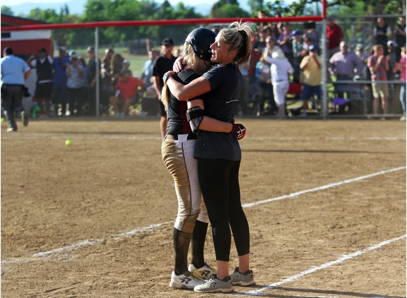DAN BROOD - Tualatin High School softball coach Jenna Wilson (right) hugs Timberwolf senior Sammi Caron following the final out in Tuesday's state playoff semifinal game at North Medford.