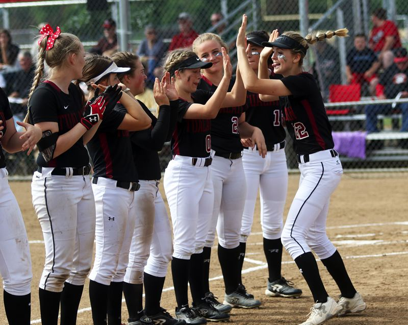DAN BROOD - Tualatin junior outfielder Ella Hillier (right) slaps hands with her teammates during pregame introductions prior to the state playoff semifinal game at North Medford.