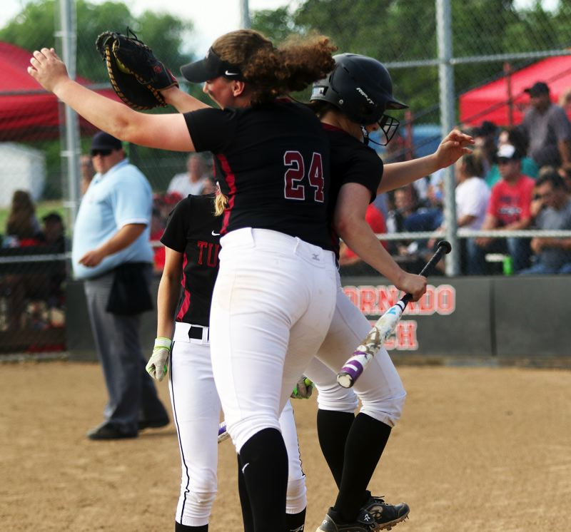 DAN BROOD - Tualatin High School sophomore Emily Johansen (24) and junior Taylor Alton celebrate after Alton scored a run for the Timberwolves, giving them a 2-1 lead, in the third inning of Tuesday's Class 6A state playoff semifinal game at North Medford.