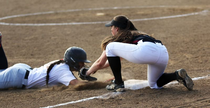 DAN BROOD - Tualatin junior third baseman Taylor Alton (right) tags out North Medford's Kylie Baker on a stolen base attempt.