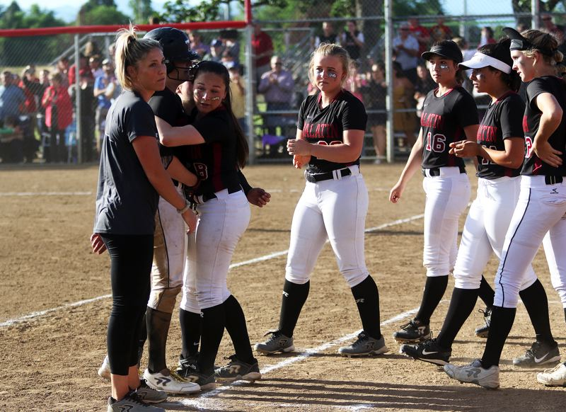 DAN BROOD - Members of the Tualatin High School softball team gather with head coach Jenna Wilson (far left) and Sammi Caron following the final out of the state playoff semifinal game at North Medford.
