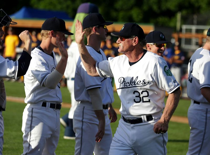 TRIBUNE PHOTO: JONATHAN HOUSE - Jeff Lahti, manager of the Portland Pickles and former World Series pitcher for the St. Louis Cardinals, gives high-fives to his players before Tuesday's game.