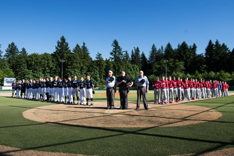 SUBMITTED PHOTO: GREG ARTMAN - Umpires and Wilsonville and Lebanon players stand in reverence during the national anthem before the game against Lebanon.