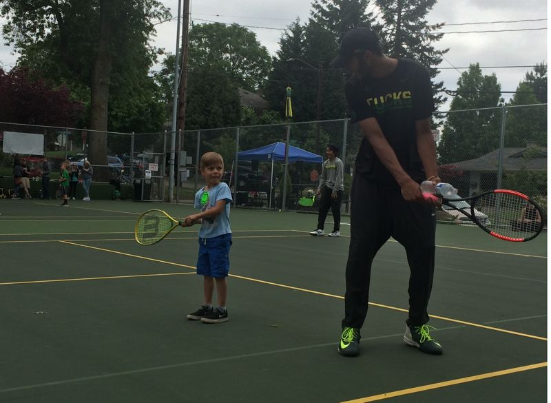 TRIBUNE PHOTO: STEVE BRANDON - Oregon Ducks tennis player Ty Gentry helps a youngster with his form at Berkeley Park.