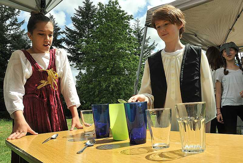 REVIEW PHOTO: VERN UYETAKE - Seventh-grader Owen Flintoff plays a tune with glass cups for Mikinzi Kelly during the Renaissance Faire on Friday at Lake Oswego Junior High.