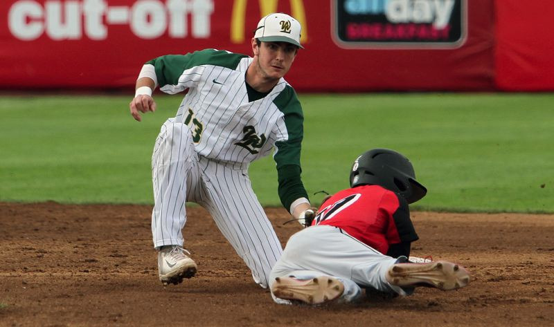 TIDINGS PHOTO: MILES VANCE - West Linn junior shortstop Jonathon Kelly tags out Clackamas Casey Peterson during his teams 5-1 loss to the Cavaliers in the Class 6A state championship game at Volcanoes Stadium in Keizer on Saturday.