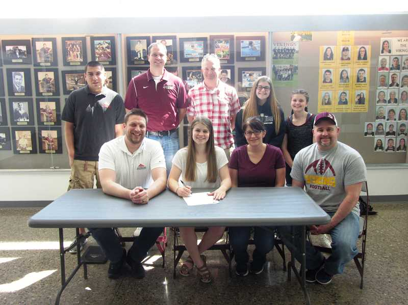 COURTESY PHOTO - Basketball player McKenzie Long signs her letter of intent at Forest Grove High with members of her family, FGHS coach Dan Lumpkin, athletic director Doug Thompson and Mt. Hood head coach Jeremy Vandenboer looking on.