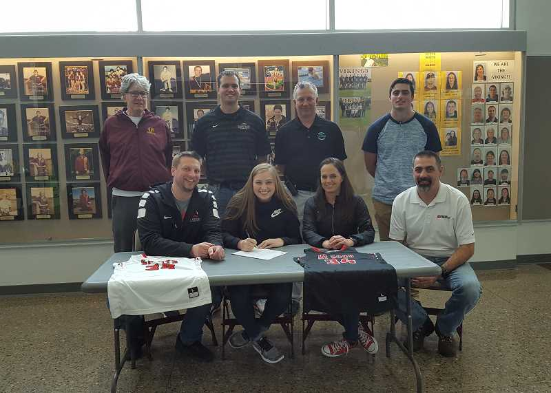 COURTESY PHOTO - Forest Grove basketball player Ashlie Collins signs her letter of intent to Mt. Hood Community College with her mom, dad and brother present in addition to FGHS coach Dan Lumpkin, athletic director Doug Thompson and Mt. Hood head coach Jeremy Vandenboer.