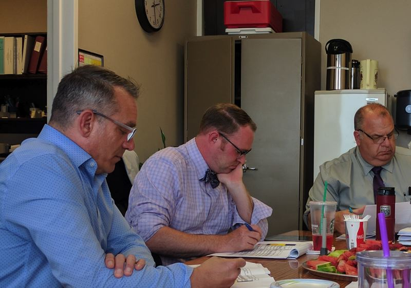 SPOTLIGHT PHOTO: COURTNEY VAUGHN - Michael Ray (left) reviews a table of CC Rider's bus routes with Columbia County Commissioners Alex Tardif (center) and Henry Heimuller during a staff meeting Wednesday, June 7. A study is underway to look at the benefits of a potential merger with Sunset Empire Transportation.