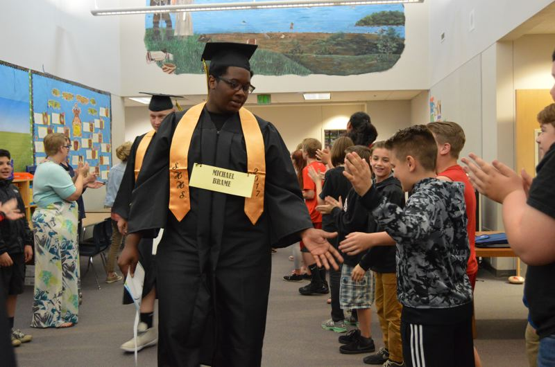 SPOTLIGHT PHOTO: NICOLE THILL - Senior Michael Brame reaches out to high five a student during the senior walk at McBride Elementary School.