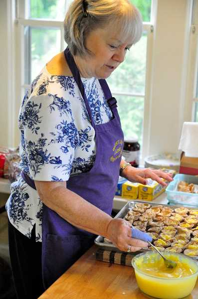 STAFF PHOTOS: LESLIE PUGMIRE HOLE - Event co-chair Nikki Landau preps the tiny lemon tarts served at the tea luncheon.