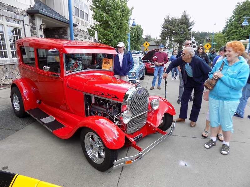 GAZETTE PHOTO: RAY PITZ - Cruisin' Sherwood attendees take a look at a beautiful red 1929 Ford Model A parked along Main Street June 10.