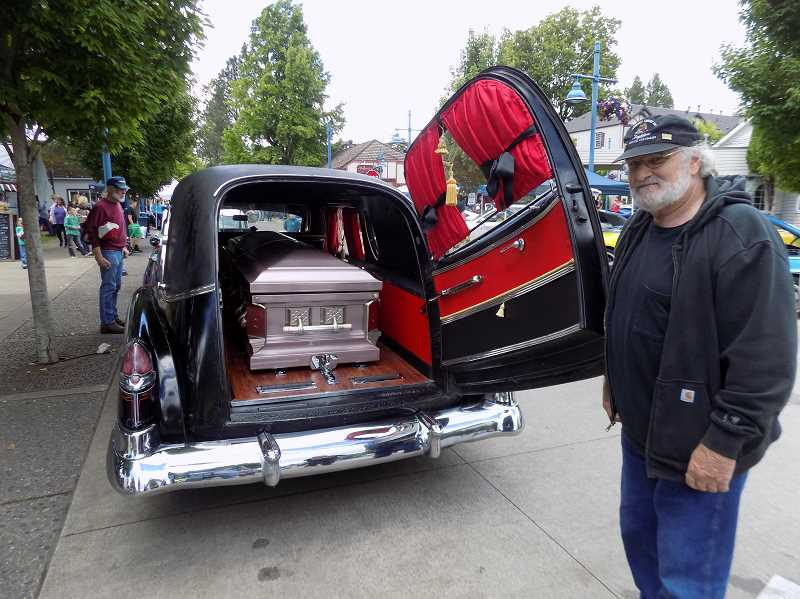 GAZETTE PHOTO: RAY PITZ - Mike Ray of Wilsonville displays the (empty) casket in the back of his renovated 1950 Cadillac hearse with the orignal engine.
