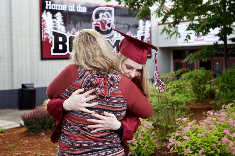 GAZETTE PHOTO: JAIME VALDEZ - Susannah Morgan hugs her mom,Kate, before joining her classmates before Sherwood High School's graduation.