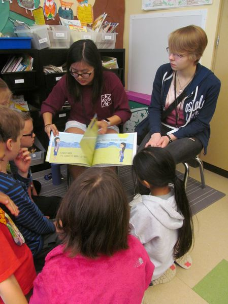 PHOTOS BY ELLEN SPITALERI - Y-Nhi Tran, 17, reads her book 'Waves,' to second graders, while Kelsey Ruhl, 18, illustrator of book, looks on.