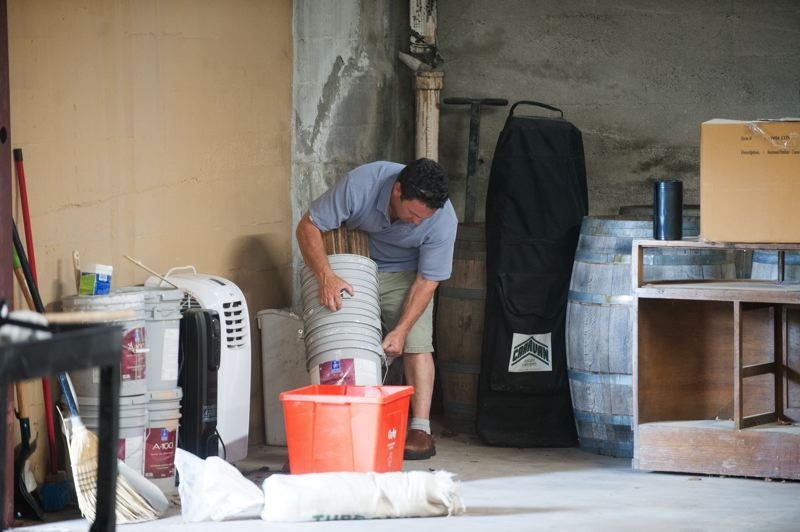 OUTLOOK PHOTO: JOSH KULLA - The owners of Calcagno Cellars envision making wine in the large building that once housed an auto garage in downtown Troutdale. Here, Frank Calcagno works in a corner of the building that also hosts a wine tasting room up front.