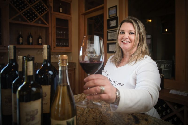 OUTLOOK PHOTO: JOSH KULLA - Kristi Calcagno offers up a glass of Calcagno Cellars cabernet franc, just one of the many varietals wine enthusiasts may sample at their new downtown Troutdale tasting room.