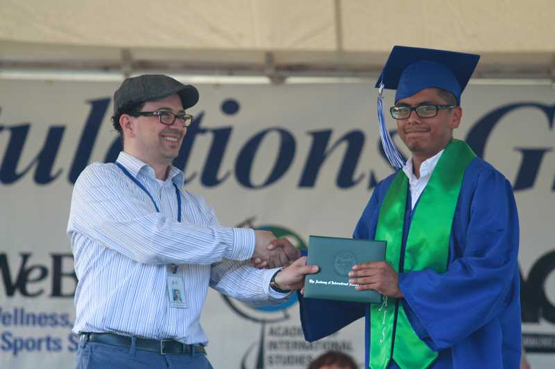 LINDSAY KEEFER - Gustavo Lopez accepts his diploma from board member Gustavo Gutierrez-Gomez at graduation. Lopez received an athletic scholarship from Clackamas Community College.