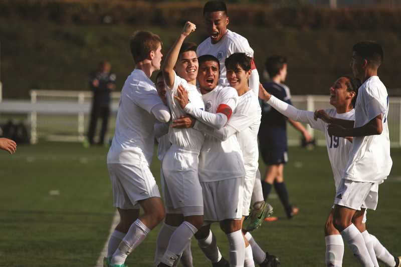 PHIL HAWKINS - The Woodburn boys soccer team celebrates the game-winning goal scored by senior Anthony Santillan (wearing the captain's band) in the title game of the 2016 5A Boys Soccer State Championships.