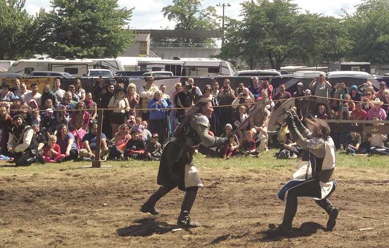 JOHN BAKER - Other faire-goers watched a late-afternoon duel between opposing factions.