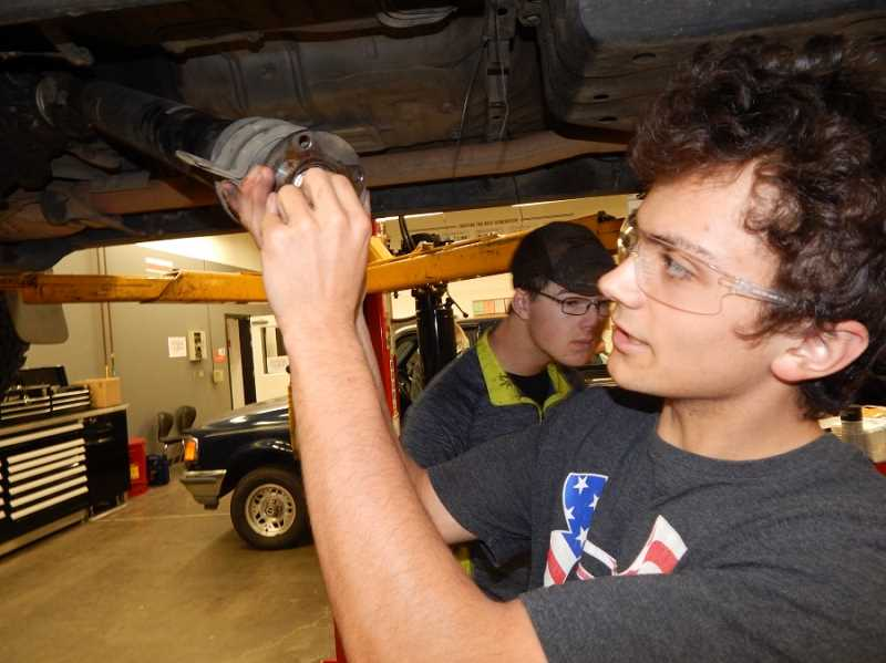 BARBARA SHERMAN - Sherwood High School student Brenton (foreground) works on his truck in the World of Speed shop assisted by his friend Brenden, noting that he prefers using a hydraulic lift to lying in the mud under his truck.