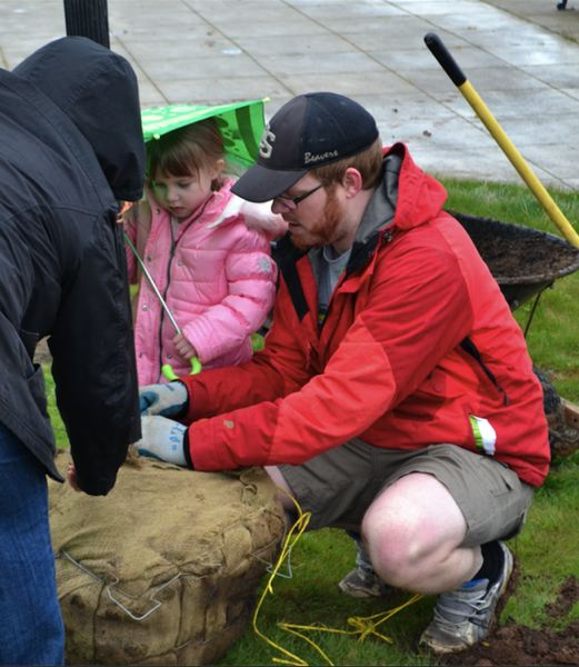 POST PHOTO: BRITTANY ALLEN - Thomas Fisher plants trees at city Arbor Week event with his three daughters.