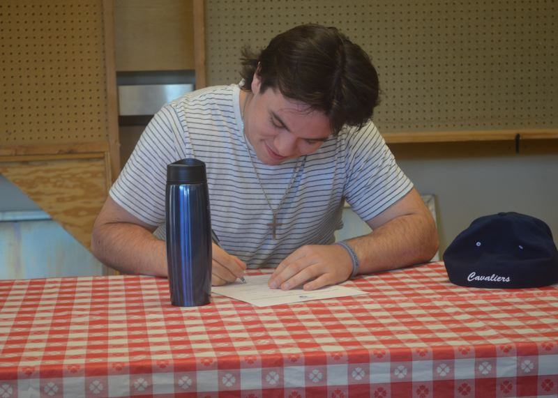 SPOKESMAN PHOTO: COREY BUCHANAN - Wilsonville baseball player Dominic Enbody signs his letter of intent to play for Concordia University at Wilsonville High School in May.