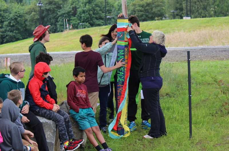 TIDINGS PHOTO: ANDREW KILSTROM - Three Rivers Charter School staff and students tie class messages to their peace pole before placing it in its final resting place Tuesday, June 13.