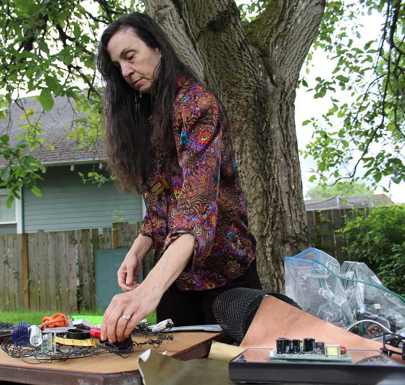 REVIEW PHOTO: SAM STITES - Artist Julie Forbes works on a piece in the backyard of her Northeast Portland home. Forbes' work incorporates items she finds from electronic recycling centers, thrift stores and even just walking around her neighborhood.