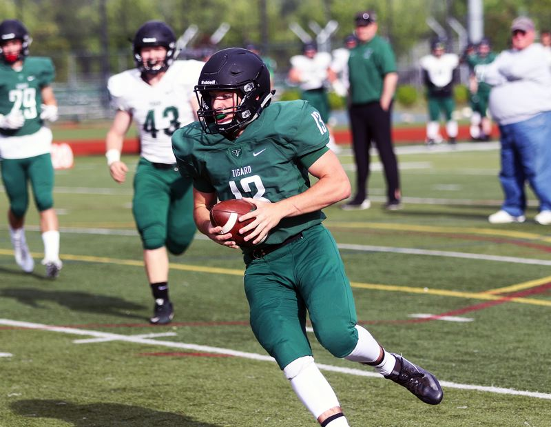 DAN BROOD - Green team quarterback Carson Crist, who threw for four touchdowns, scrambles during play in the Tigard Chicken and Bean Bowl.