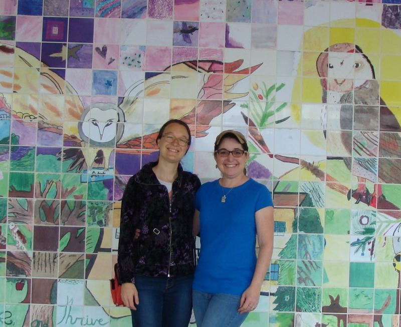 COURTESY PHOTO - Veronica Reeves and Jennifer Hanson stand in front of a new mural that will be officially unveiled at Otto Petersen Elementary School next week. Students at the school helped design the mural and handcraft tiles to make up the mosaic pattern.