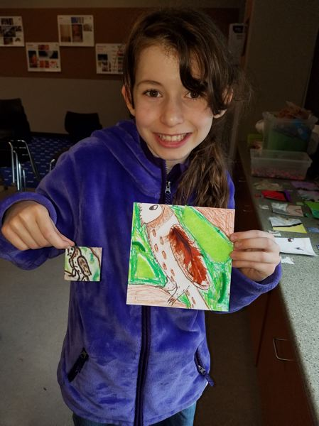 COURTESY PHOTO - Cordelia Hanson, a sixth-grader at Otto Petersen Elementary School and the daughter of Jennifer Hanson, holds up a 2-by-2-inch paper square which has an original drawing on it, and a 6-by-6-inch square which she transposed using paints and 3-D objects. The larger square was then scanned and printed on a ceramic tile for the mural.