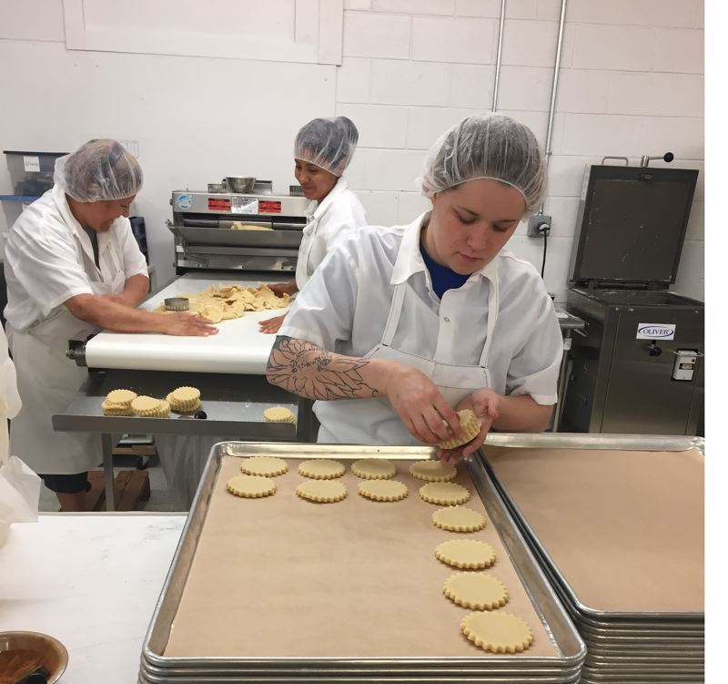 PHOTO CREDIT: BRYAN AULICK - A worker at McTavish Cookie Company near Gateway lays out shortbread for a baking. New food safety rules will take the company a lot of time and money to follow, according to owner Denise Pratt, but she believes they are good for the industry in the long run. (Above and below) Workers at food processing plants will have to clean more, and document their cleaning.