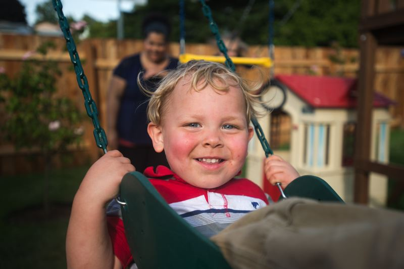 OUTLOOK PHOTO: JOSH KULLA - Summer Hermann gives her foster child E a push on the swings.