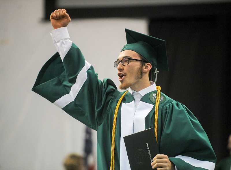 OUTLOOK PHOTO: JOSH KULLA - Reynolds High School class of 2017 graduate Seth Dudley pumps his fist at the crowd upon receiving his diploma Thursday night at the school's commencement exercise at the Memorial Coliseum.