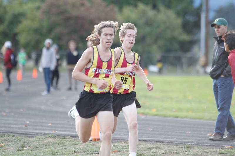 NEWS-TIMES PHOTO: WADE EVANSON - Max and Quincy Norman run side-by-side during a home meet versus West Salem and Sprague.
