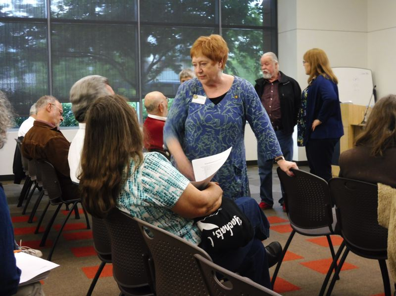 TIMES PHOTO: DANA HAYNES - Rep. Margaret Doherty of Tigard, center, talks to constituents while Sen. Chuck Riley of Hillsboro and Rep. Sheri Malstrom of Beaverton, behind her, chat with Rep. Mitch Greenlick, seated. An estimated 50 people attended the town hall.