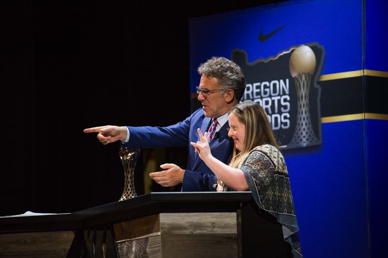 TRIBUNE PHOTO: ADAM WICKHAM - Special Olympics skier Mandi Durfee of Elgin waves to her family during her acceptance of the Lou Burge Special Olympics Athlete of the Year Award, presented by Oregon Sports Awards host Neil Everett on ESPN on Sunday at Nike.